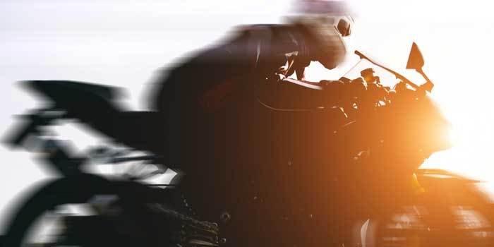 Verschwommene Aufnahme eines Motorradfahrers während der Fahrt.