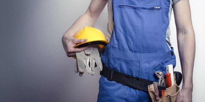 Mann trägt Blaumann und Werkzeuggürtel und trägt Helm und Handschuhe in der Hand
