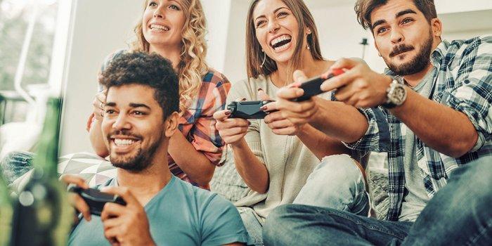 Freunde sitzen auf dem Sofa und spielen gemeinsam ein Computerspiel