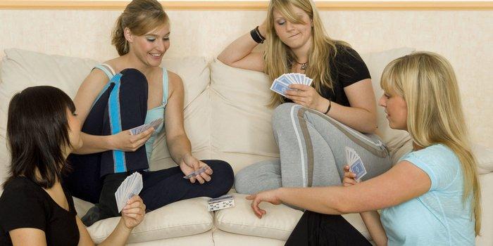 Freunde sitzen gemütlich zusammen und spielen Karten