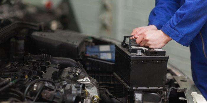Eine Autobatterie wird aus dem Motorraum entfernt