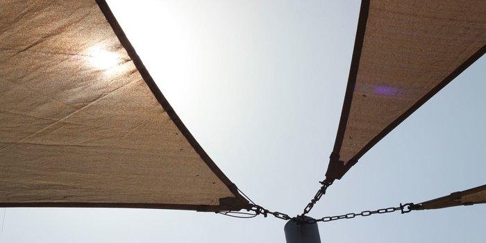 Ansicht eines Mastes, an den mehrere Sonnensegel befestigt sind