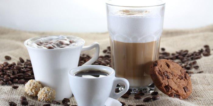 Verschiedene Kaffeespezialitäten zwischen frischen Kaffeebohnen