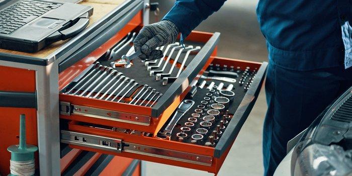 Handwerker sucht sich Werkzeug aus einem Werkstattwagen