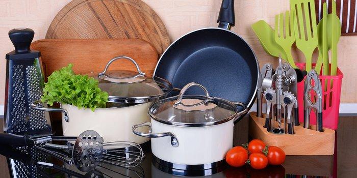 Küchenzubehör wie Töpfe, Pfannen, Besteck und Küchenhelfer auf einer Arbeitsplatte