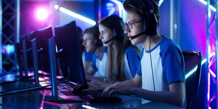 Mehrere Personen sitzen vor ihren Rechnern und sind in ihrem Spiel vertieft