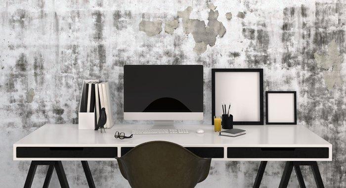 Designer-Schreibtisch mit All-in-One-Computer und vielen Utensilien