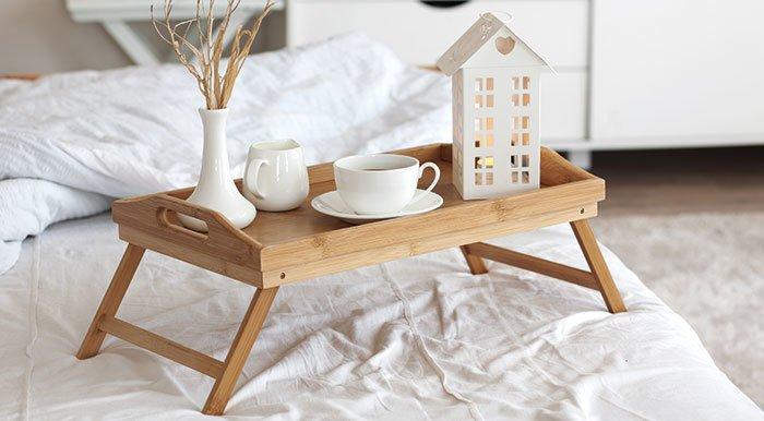 Aufnahme eines Tabletts mit Frühstück darauf im Bett.