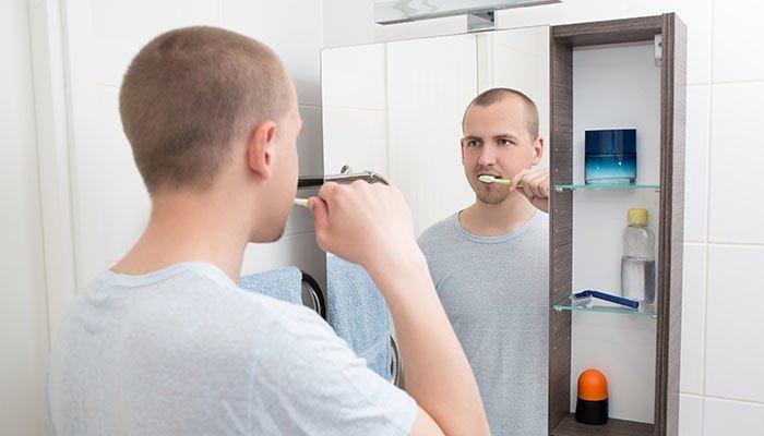 Aufnahme eines Mannes, welcher sich vor einem Spiegelschrank die Zähne putzt.
